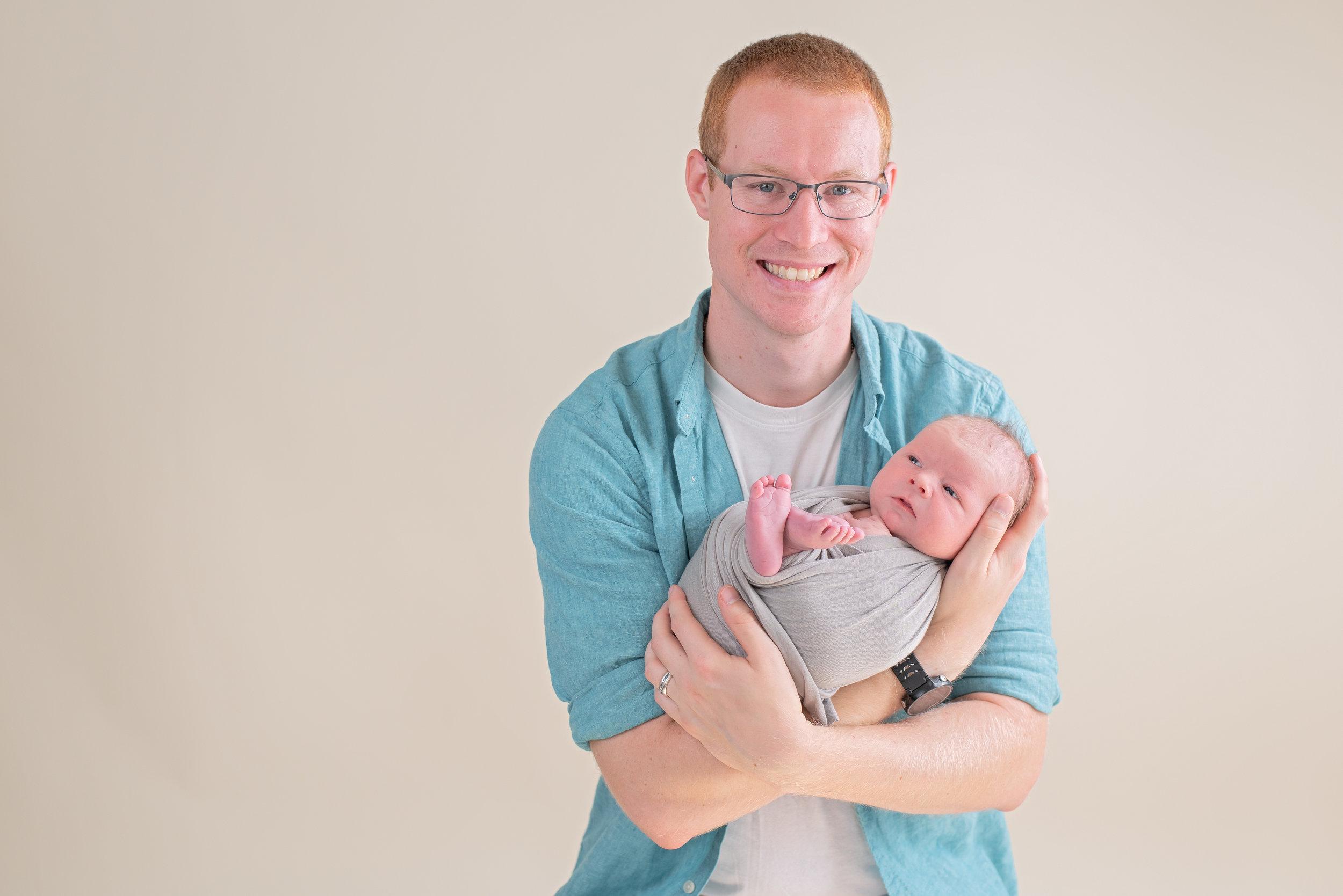dad holding newborn pose