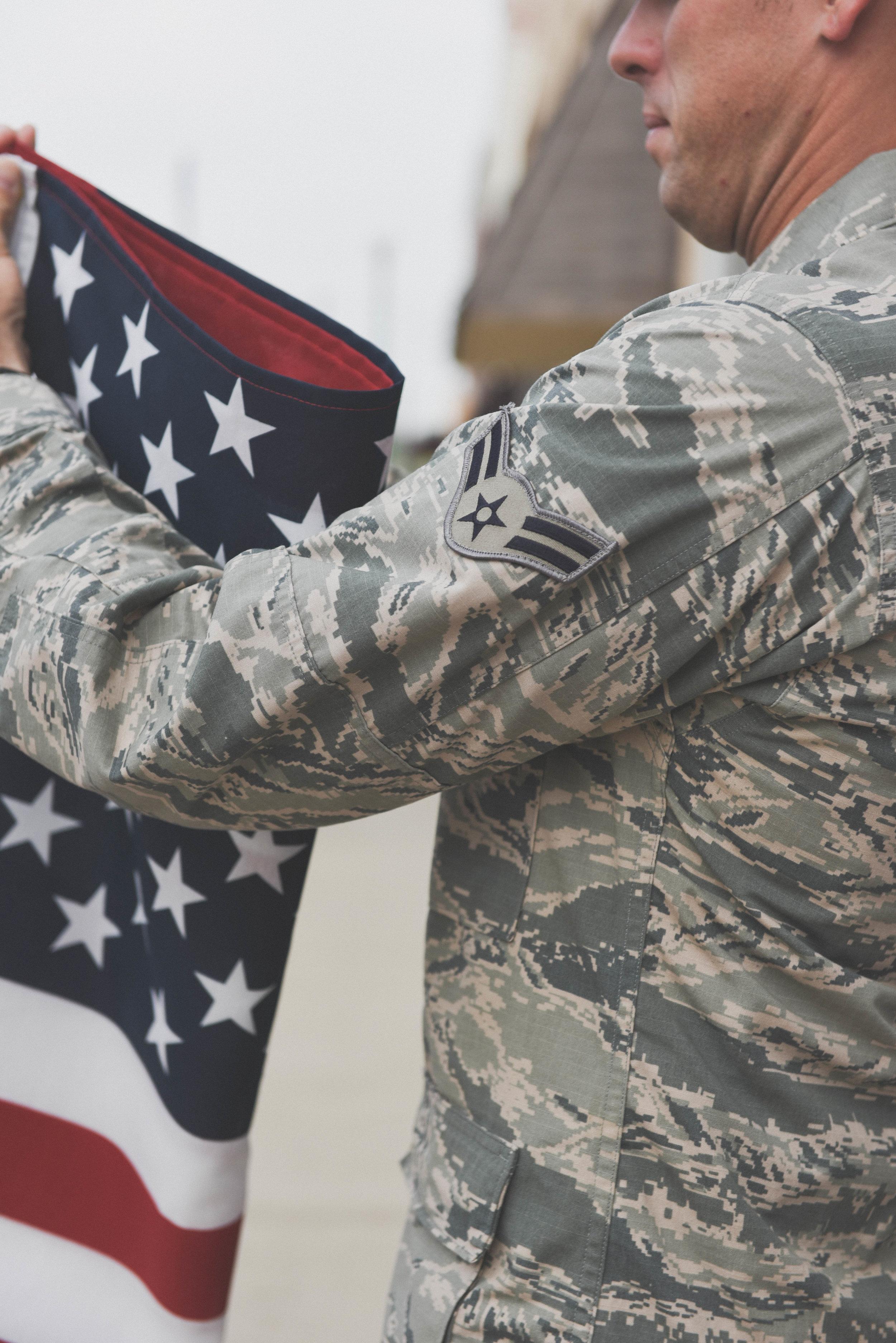 man folding flag