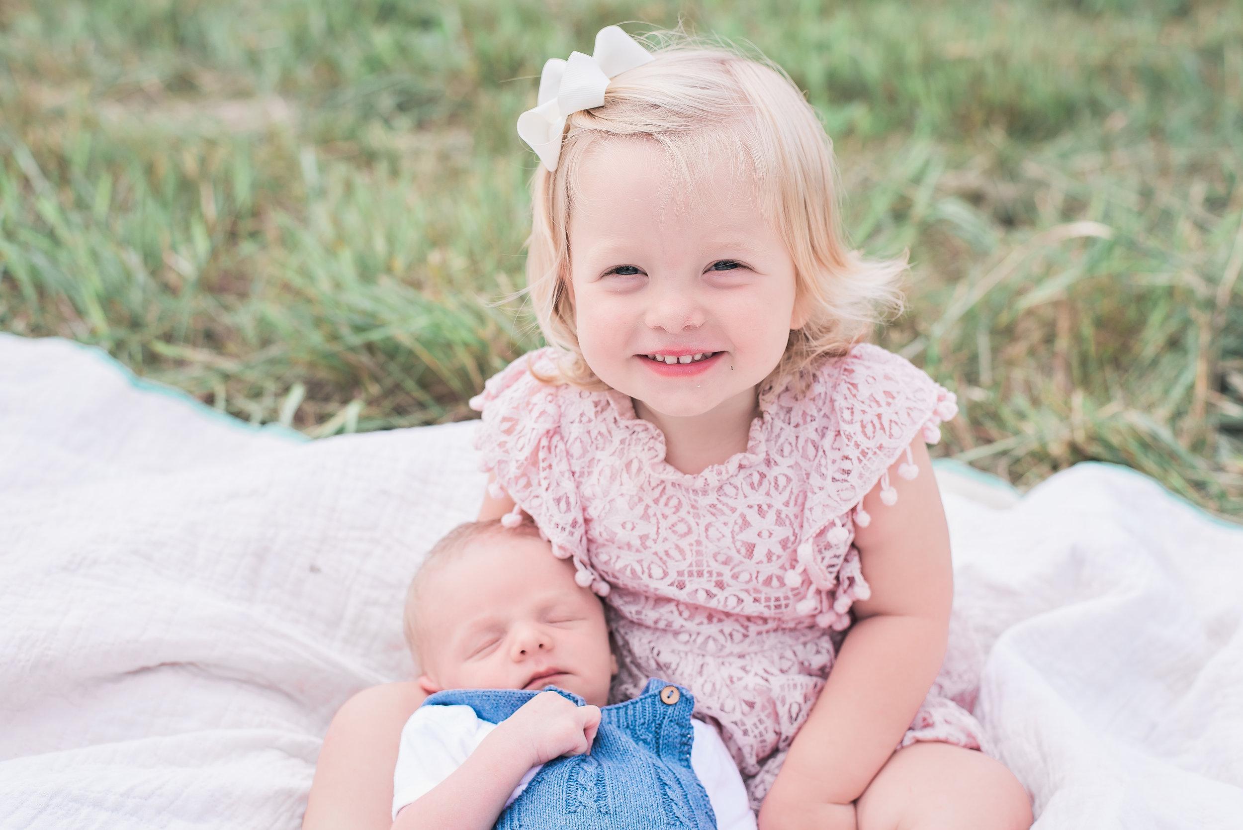 newborn sibling shot outdoors