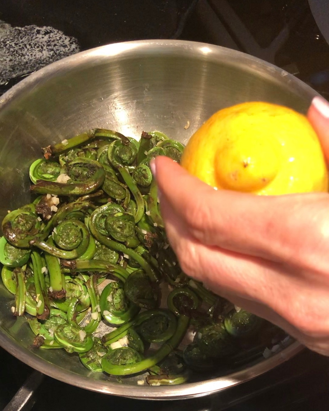 Stir in the fiddleheads and add the lemon juice, mixing everything together.