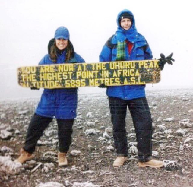 """#TBT to when I was a mountain woman (and a brunette 😂👩🏻) and decided that I was going to climb Mt. Kilimanjaro, one of the """"seven summits"""" and the highest peak in Africa. . This was so long ago that there wasn't even a sign at the top (nor Instagram or digital cameras). I got to commemorate my accomplishment by holding up a heavy, weathered, wooden board that confirmed I set foot on Uhuru Peak, the highest point in Africa. . But don't let my happy, care-free smile fool you. After a 4-day ascent on little to no sleep, and no air (think sprinting while breathing through a cocktail straw), I was barely keeping it together. This picture was taken around 8am after a grueling 8hr trek to the summit (almost 20,000ft) and I remember that the only thing keeping me from lying down on the frozen ground and taking a nap was Robin, my new friend from Amsterdam (holding the other end of the sign), whom I met on the mountain. I may have never made it down without him, although getting to the top was never in question. I was going to do it if they had to carry me off the mountain (probably not the smartest attitude at such altitude, but I am relentless when I set a goal). . Why did I do it? Simply put, I love a good challenge. After all, how do you know what it is you're capable of if you don't challenge yourself? If you don't set any goals? If you don't take any risks? How do you know your own worth? . Life is short and as you get older, you will only regret the things you didn't do, didn't say, abs didn't go for. . As Albert Einstein famously said, """"A ship is always safe at shore, but that's not what it is built for."""" . When was the last time you did something to challenge yourself? When was the last time you felt alive? #justdoitalready . . . . . #climbeverymountain #ifitdoesntkillyou #challengeyourself #setgoals #takerisks #lifeisforliving #throwbackthursday #goals #mtkilimanjaro #uhurupeak #kilimanjaro #kilimanjaro1997 #lifeisshort #girlswhoclimbmountains #mountainwoman #7summ"""