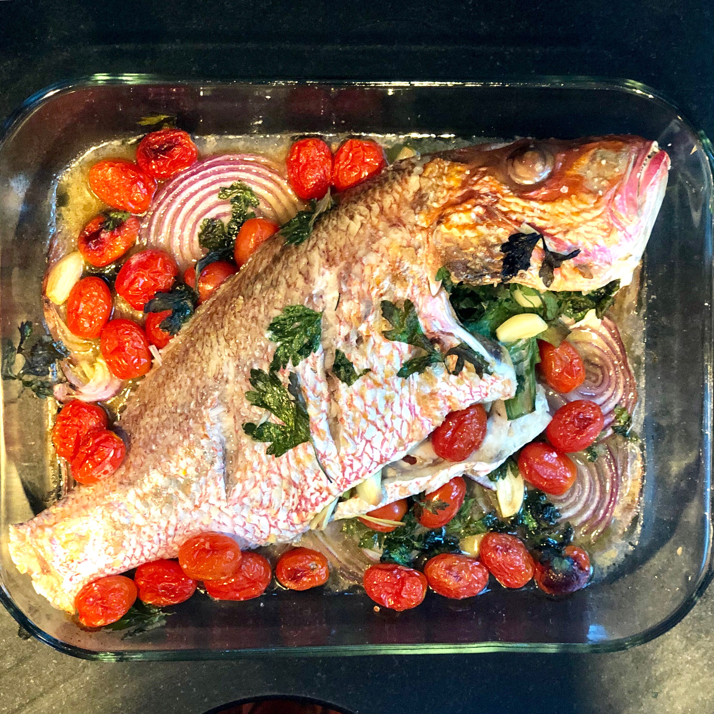 10. Once your timer has chimed after 25-30 minutes, turn your oven to broil and leave the fish in for another 5-7 minutes, until the top has browned a bit.  11. Remove the fish from the oven and debone it on a large wooden cutting board.