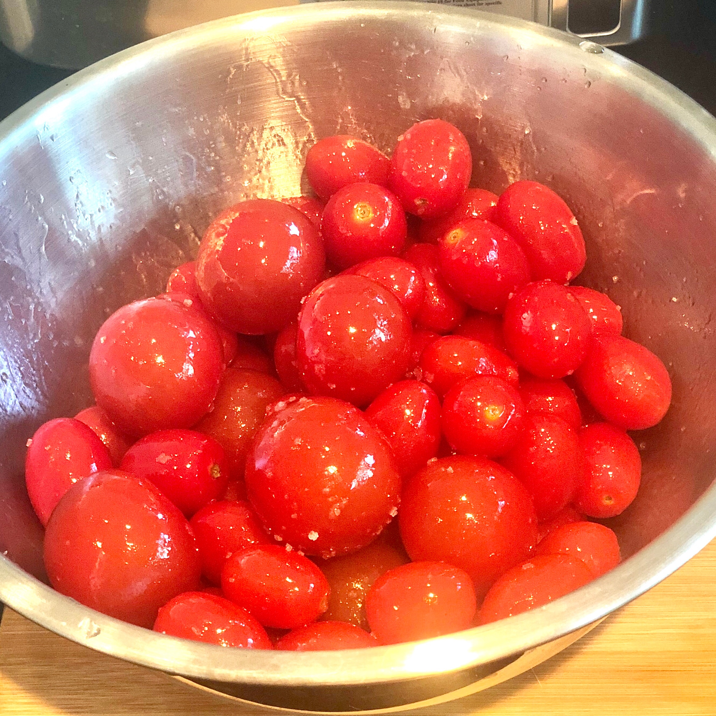 6. In a bowl, toss the whole cherry tomatoes in olive oil and salt. Scatter them around the pan.  CLICK HERE to buy a set of Stainless Steel mixing bowls  on Amazon.