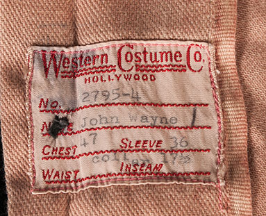 Label from John Wayne movie shirt by Western Costume Co. Estimate $3,000-4,000.