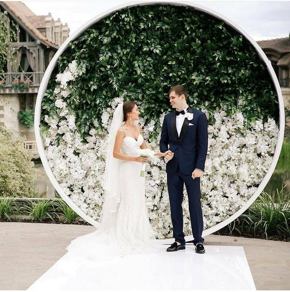 circular-backdrop-adorned-with-greenery-and-white-hued-bloom.jpg