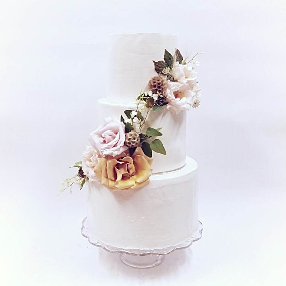 simple buttercream wedding cake with fresh flowers