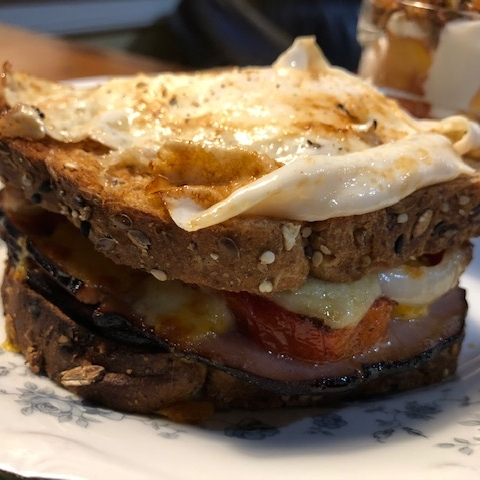 """Lydia's take on a Croque Madame: Whole Grain """"Dave's Killer Bread"""" paired with ham and cheese topped with a healthier Dijon sauce, combined with broiled Jersey tomatoes and caramelized onions."""