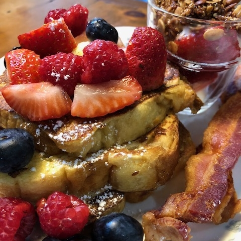 """Our version of French Toast made with """"Craque""""lin (a Belgian brioche) topped with real maple syrup and fresh berries and served with our yogurt granola parfait."""