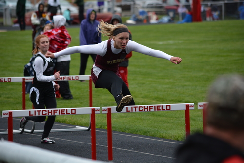 Potterville track and field: student jumping over a hurdle