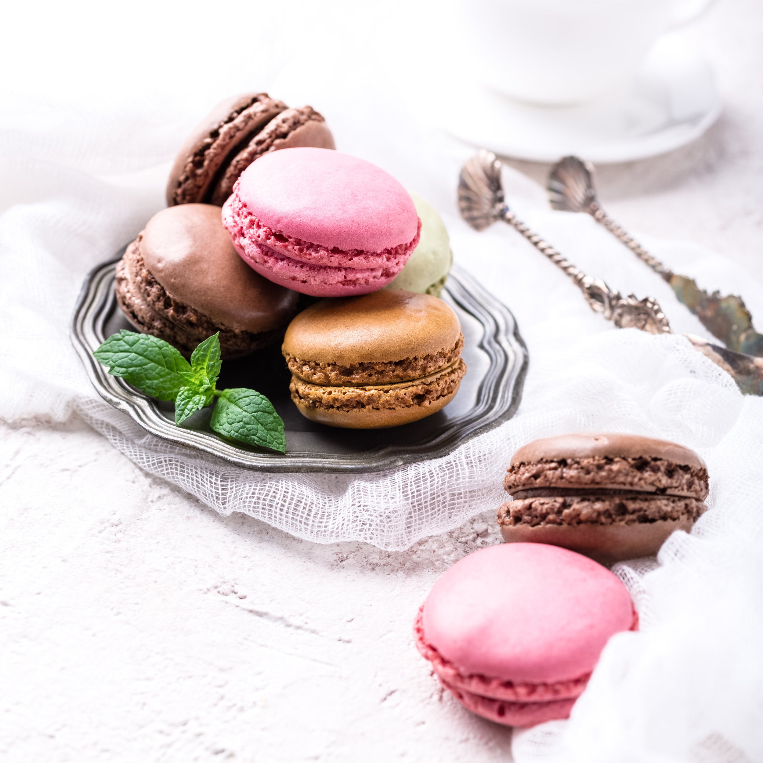 Colorful almond cookies macaron or macaroon on light background, vintage card, holiday food concept, copy space for text.