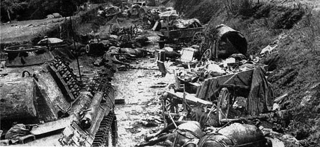 Destroyed and abandoned German armor and motor transport litter a road in the region of Falaise.
