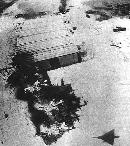 Taken from a low-flying IAF Mirage (whose shadow is visible at the bottom of the picture), three MiG-21s lie destroyed in front of a hangar at Inchas airfield. Photo credit:http://www.oocities.org/capecanaveral/hangar/2848/opera6_2.htm