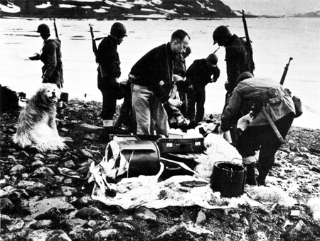 Members of the Sled Patrol examine captured parachute equipment at the site of an abandoned German weather station.