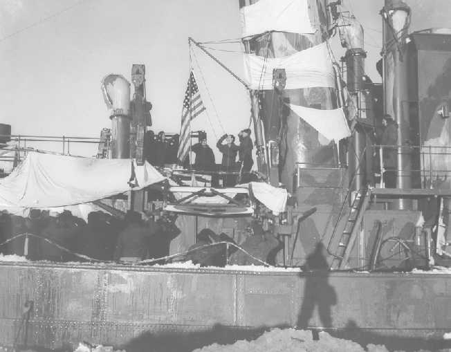 Members of the Coast Guard raise the flag aboard the Externsteine on October 16, 1944. Source: US Coast Guard.