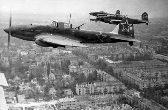A group of Il-2M3s fly low above a devastated city.