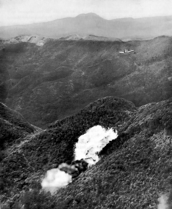 An F4U Corsair drops napalm on a Japanese position while operating in close air support of Marine forces on the ground.