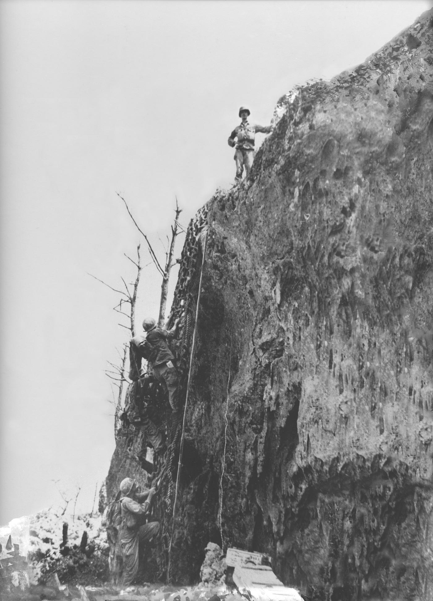 Doss stands at the top of Maeda Escarpment after placing cargo nets on the side of the cliff- Doss was one of the volunteers who carried the net to the top.