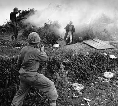 Two Marines carefully watch an Okinawan civilian surrendering.