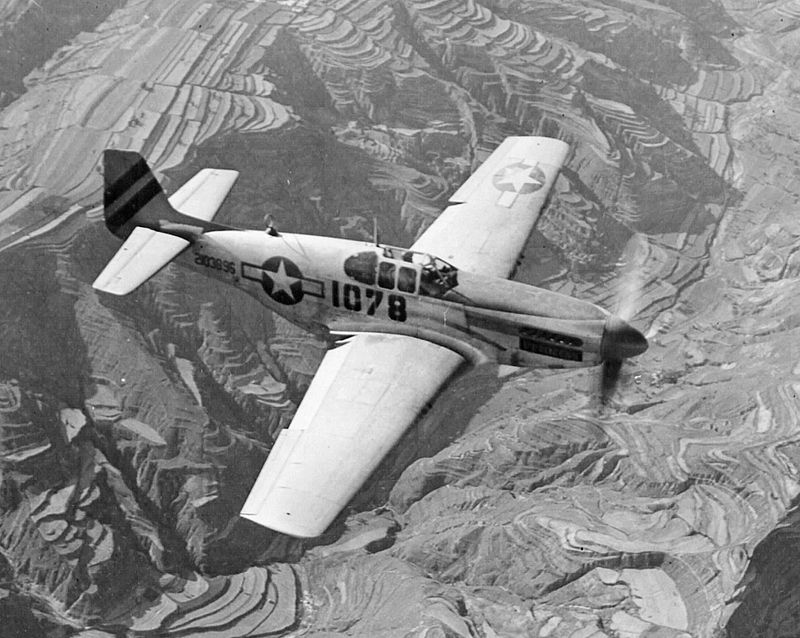 A Merlin-engined P-51B Mustang in flight. This aircraft uses the earlier framed canopy, which was replaced by the Macolm hood, a rounded Plexiglas canopy that omitted metal frames and allowed for increased visibility. Source: Wikipedia.