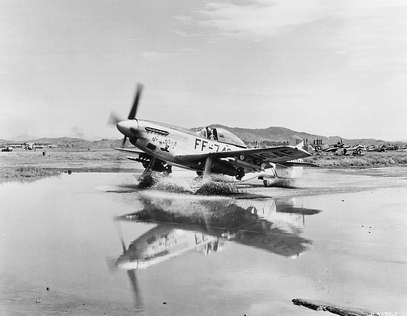 "A USAF F-51D (DURING THE INTERWAR PERIOD, A REDESIGNATION OF FIGHTER AIRCRAFT FROM ""PURSUIT"" TO ""FIGHTER"" OCCURRED) TAXIES THROUGH A PUDDLE IN KOREA. THIS AIRCRAFT IS ARMED WITH 2 500 LBS BOMBS, 4 2.75 INCH ROCKETS, AND SIX .50 CALIBER MACHINE GUNS. SOURCE: WIKIPEDIA."