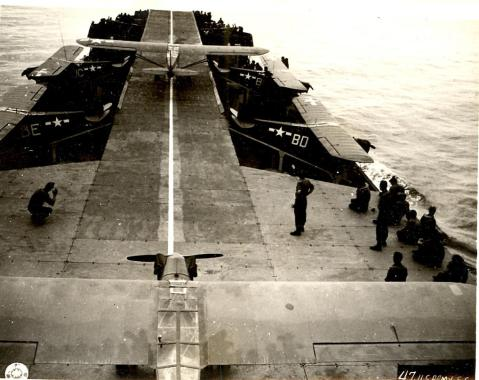 """A view from the deck of an LST converted for use as an """"aircraft carrier"""". The aircraft in this picture are Piper L-4 observation aircraft, frequently used for artillery spotting."""
