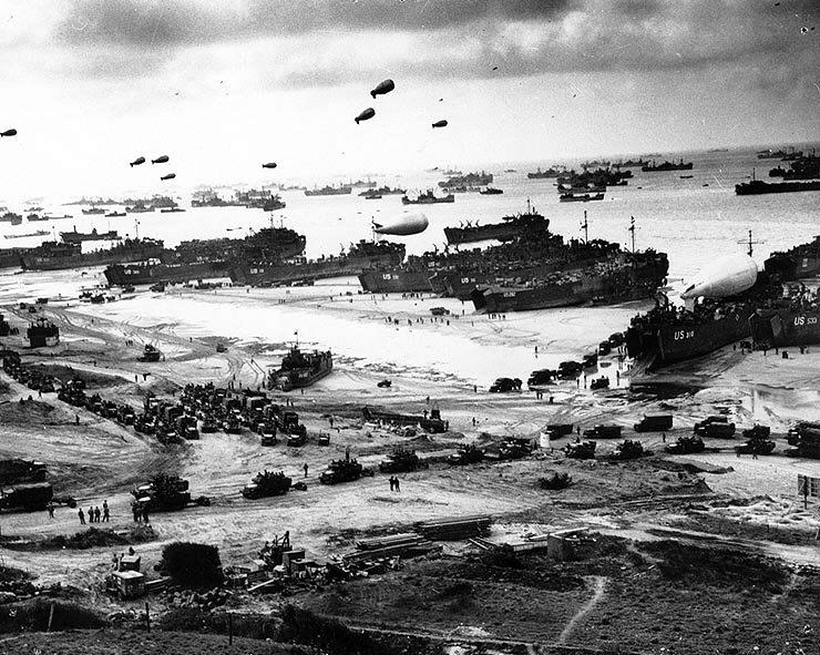 One of the most iconic images of the war, this photograph shows numerous LSTs offloading men and vehicles at the beaches of Normandy not long after D-Day. Photo source: Wikipedia.