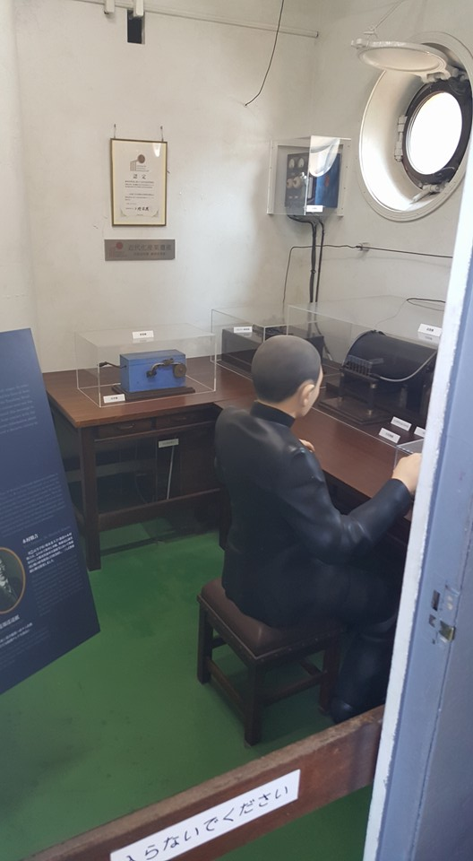 A TYPICALLY RESTORED ROOM ON BOARD THE MIKASA, IN THIS INSTANCE THE COMMUNICATIONS ROOM. A NUMBER OF ARTIFACTS ARE ON DISPLAY WITH THE AID OF PLACARDS. PHOTO: AUTHOR.