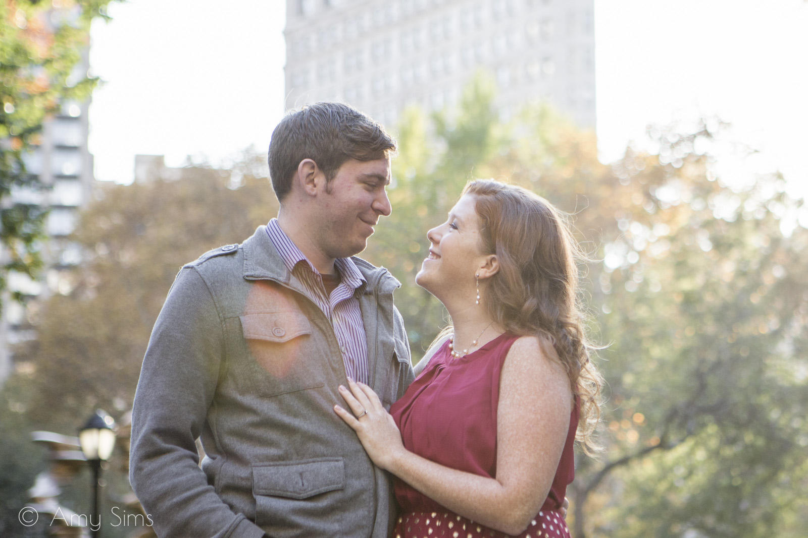 Couple smiles at each other with Flatiron Building in background | Madison Square Park Engagement | NYC Engagement | Ashley & Nick's Engagement | Amy Sims Photography