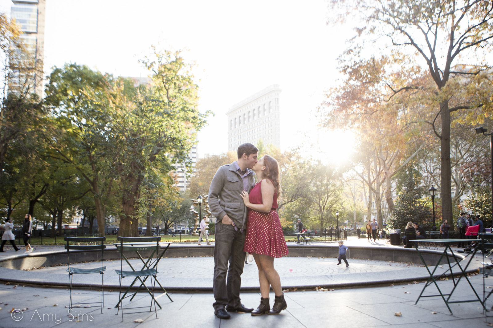 Couple share a kiss in Madison Square Park, with Flatiron Building behind them | Madison Square Park Engagement | NYC Engagement | Ashley & Nick's Engagement | Amy Sims Photography
