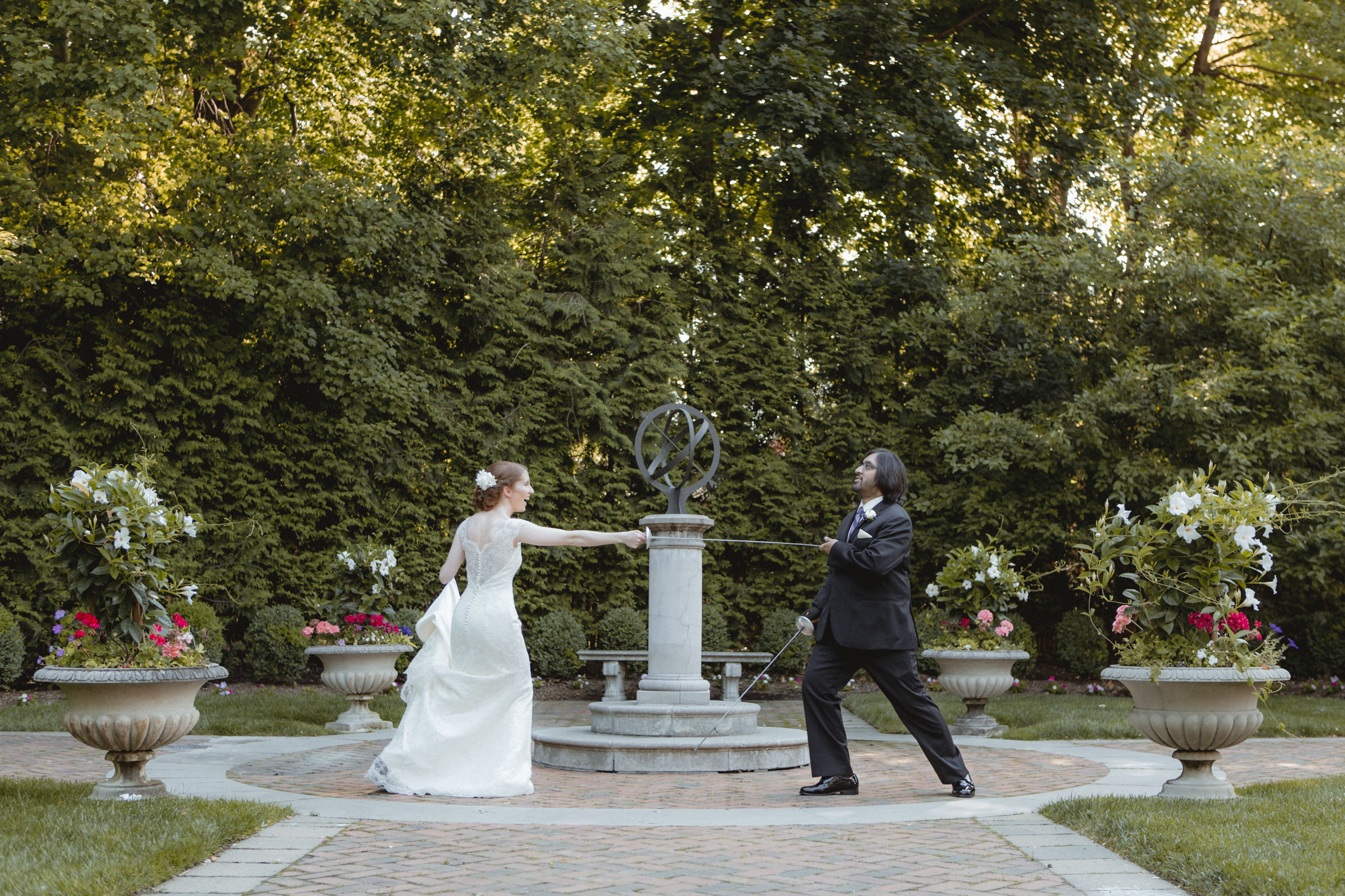Bride and groom fence with swords, she's winning - - Estate at Florentine Gardens wedding - Hudson Valley Wedding - Kelsey & Anish's wedding - Amy Sims Photography