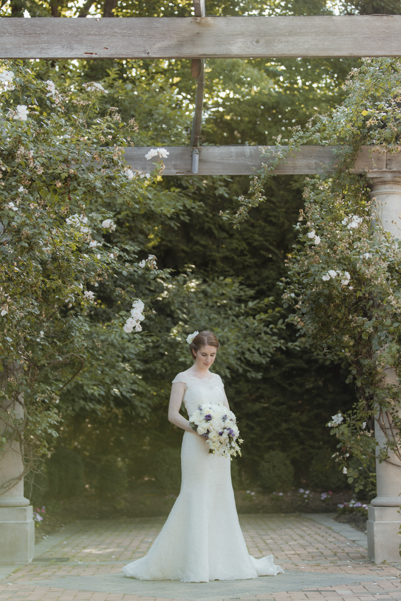 Bride stands in romantic garden wearing Augusta Jones, lace gown - Estate at Florentine Gardens wedding - Hudson Valley Wedding - Kelsey & Anish's wedding - Amy Sims Photography