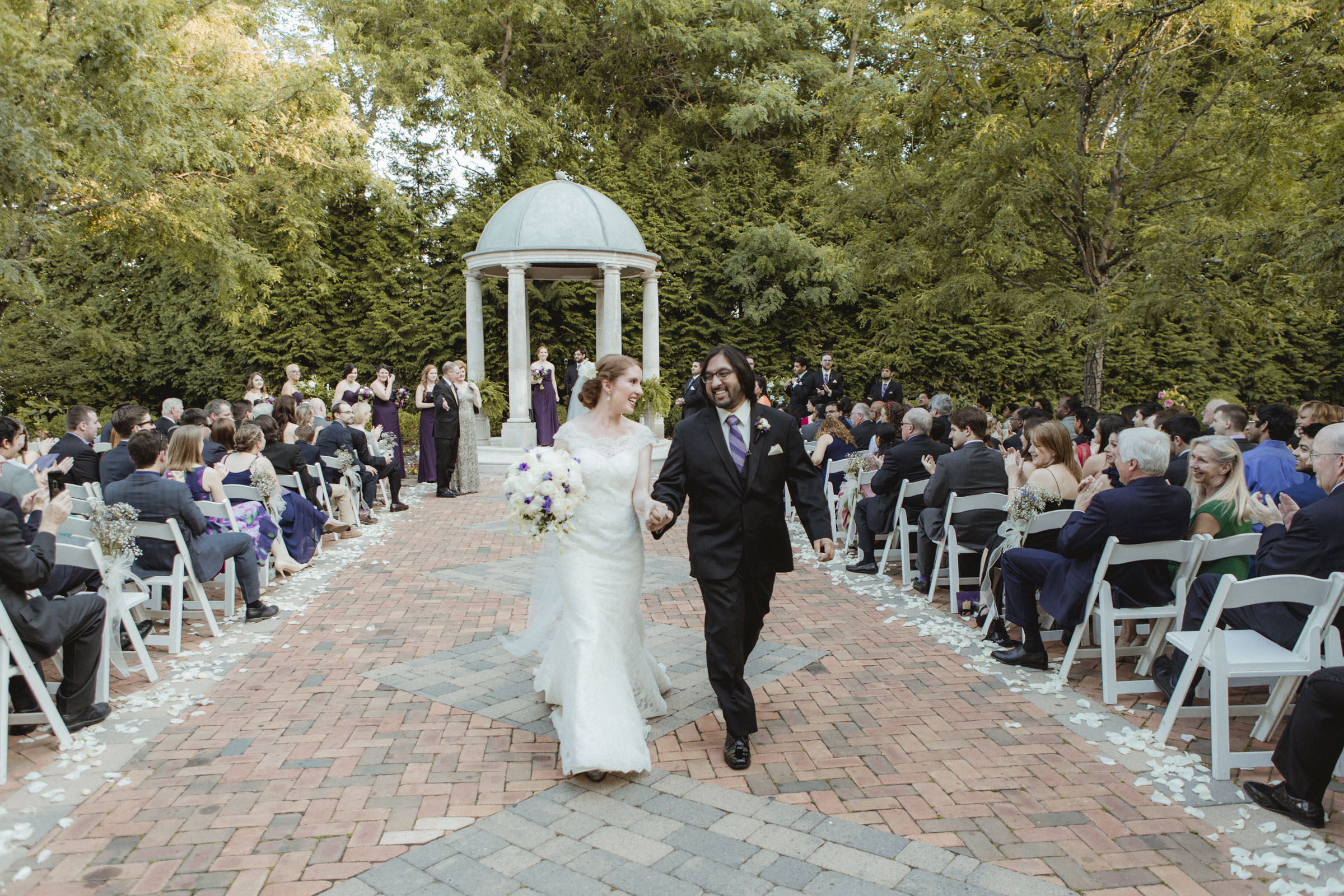 Couple smiles at each other as they come back down the aisle - Estate at Florentine Gardens wedding - Hudson Valley Wedding - Kelsey & Anish's wedding - Amy Sims Photography