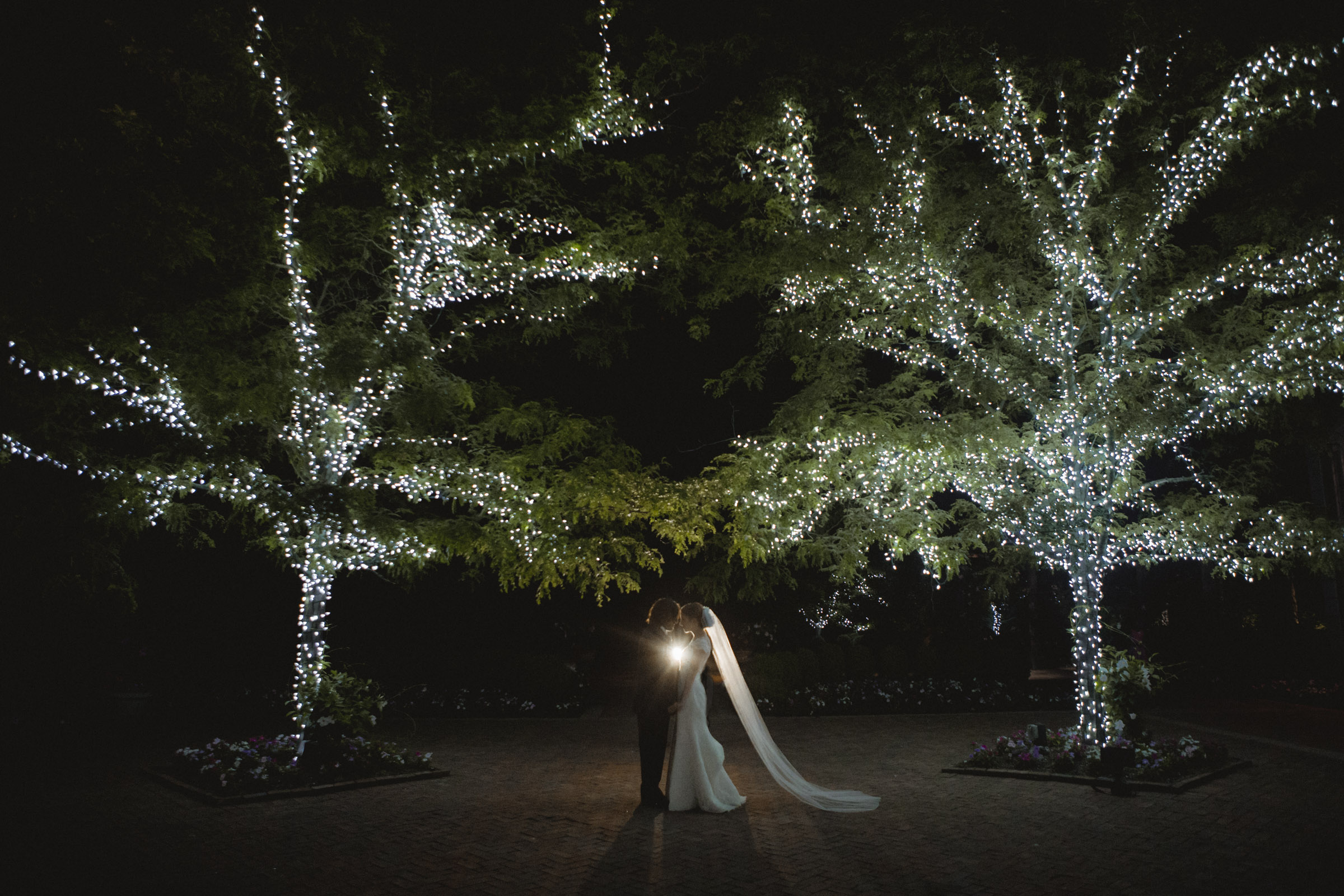 Couple stands under trees lit with twinkle lights - Estate at Florentine Gardens wedding - Hudson Valley Wedding - Kelsey & Anish's wedding - Amy Sims Photography