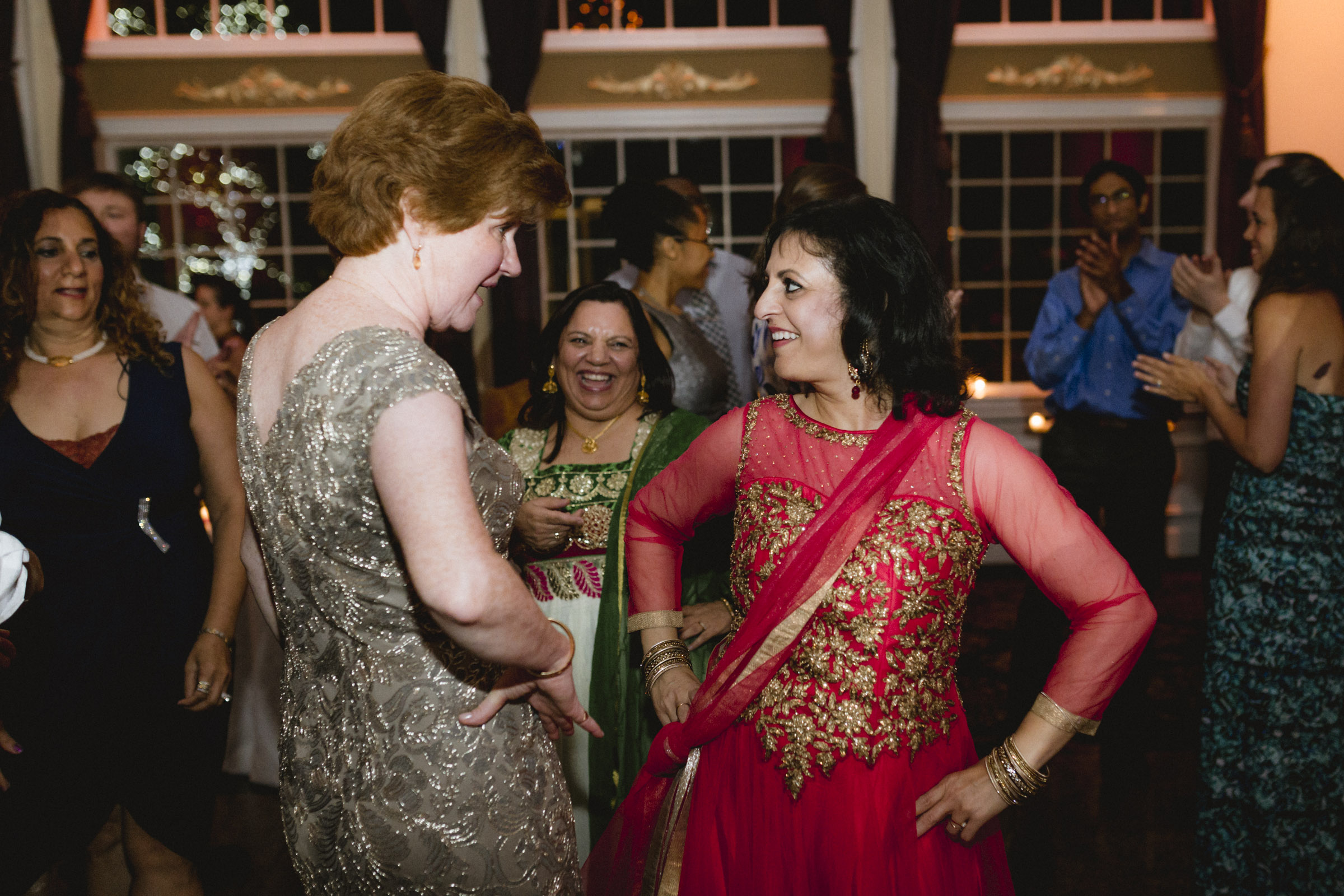 Indian woman teaches mother of bride an indian dance move - Estate at Florentine Gardens wedding - Hudson Valley Wedding - Kelsey & Anish's wedding - Amy Sims Photography