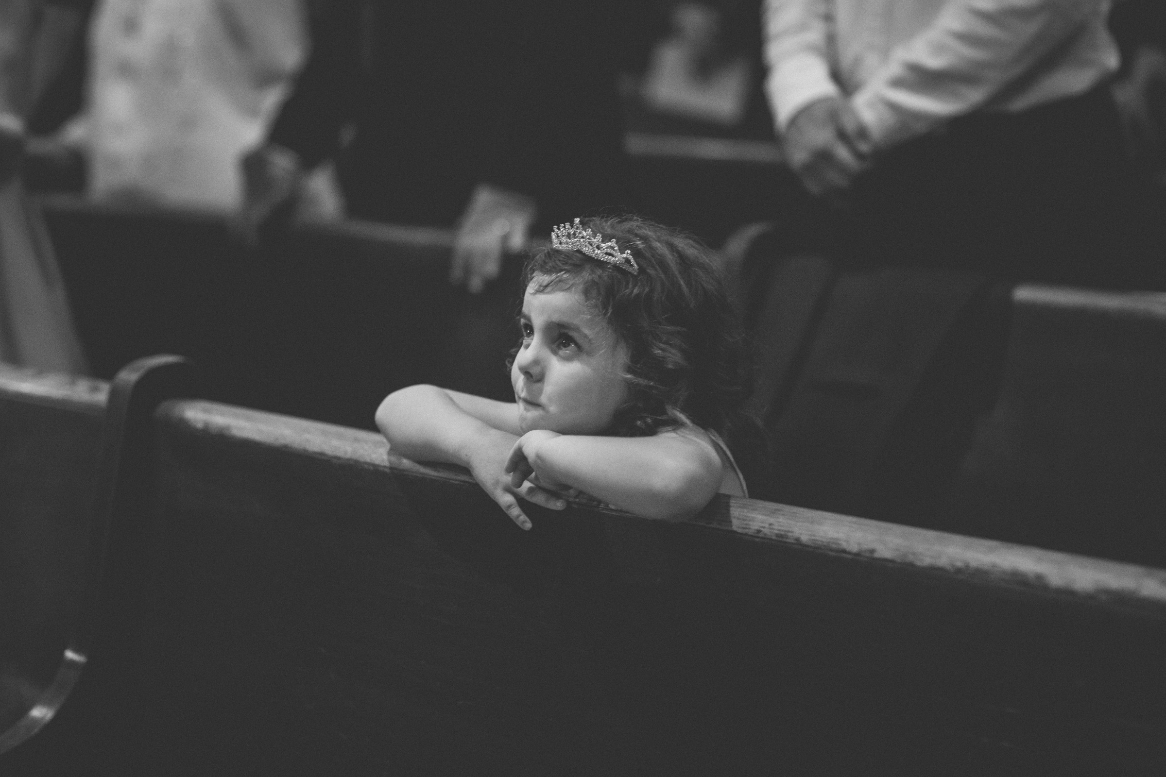 Adorable little girl looks up at couple getting married leaning on pew | Our Lady of Pompeii wedding | Manhattan wedding | Bronx Wedding | Cathy & Antonello's wedding | Amy Sims Photography