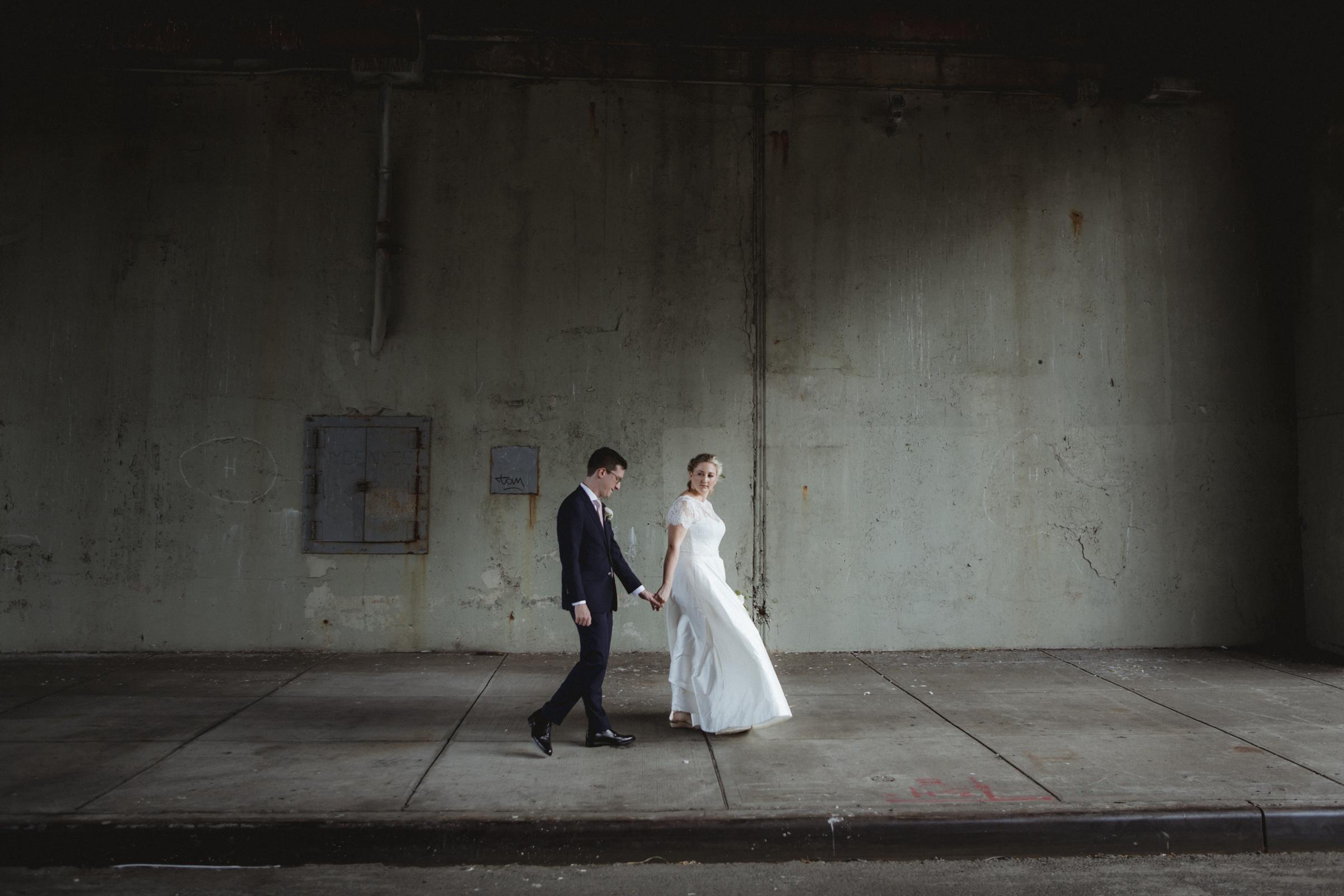 Amy Sims Photography | Bride and Groom walk hand in hand under shaded bridge | Brooklyn Wedding | Box House Hotel Wedding