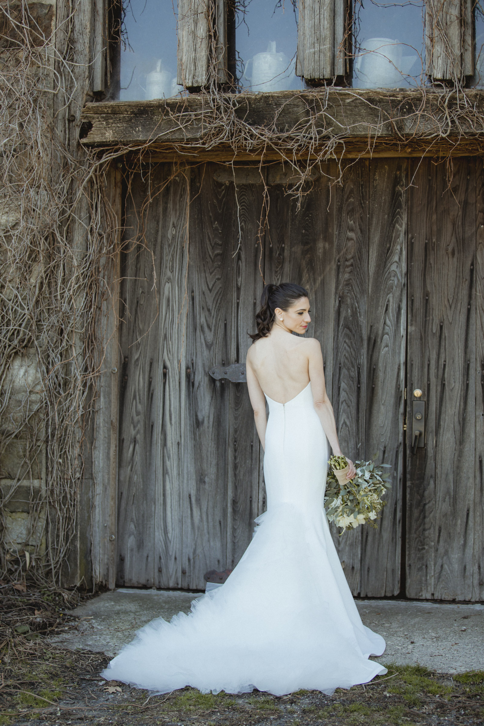 Amy Sims Photography | Bride stands in front of barn doors holding her bouquet | Blue Hill Farm Wedding | Westchester Wedding Photographer | New York Wedding Photographer