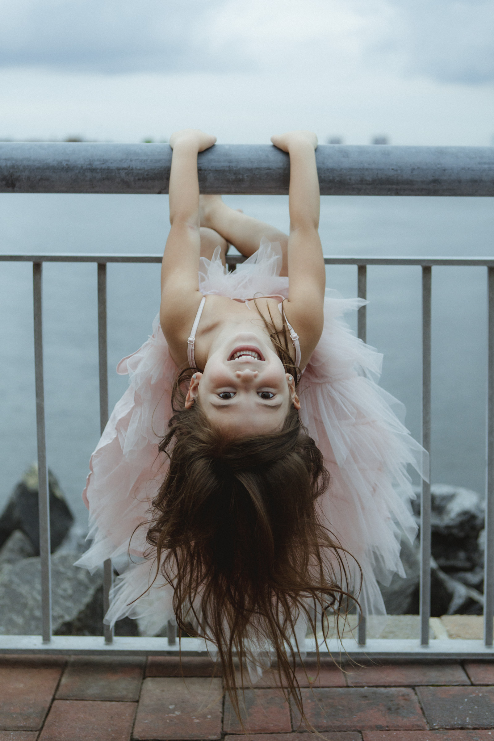 Amy Sims Photography | Flower girl playfully hangs upside down off of railing | Brooklyn Wedding Photographer | Liberty Warehouse Wedding