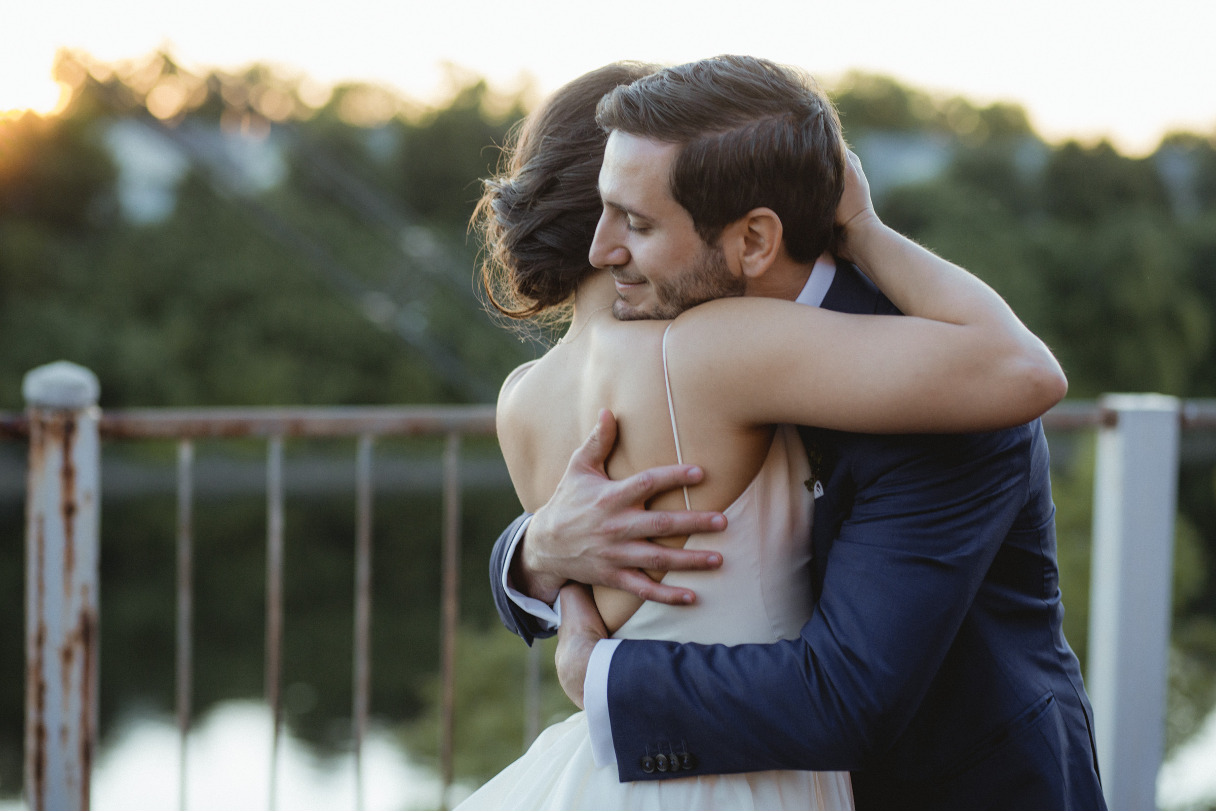 Amy Sims Photography | Groom smiles peacefully as he hugs his bride close as sunset | Upstate New York Wedding Photographer