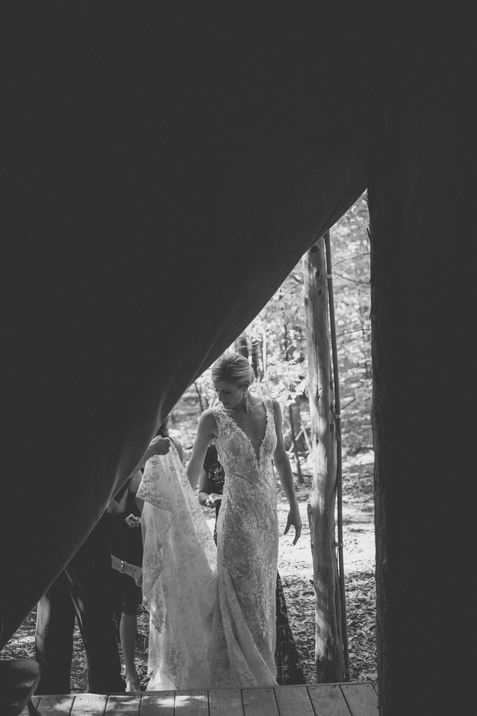 Amy Sims Photography | Bride picks up the train of her dress framed in a dark tent opening | Emmerich Tree Farm Wedding | black and white photography | Hudson Valley Wedding Photographer | black and white wedding photography