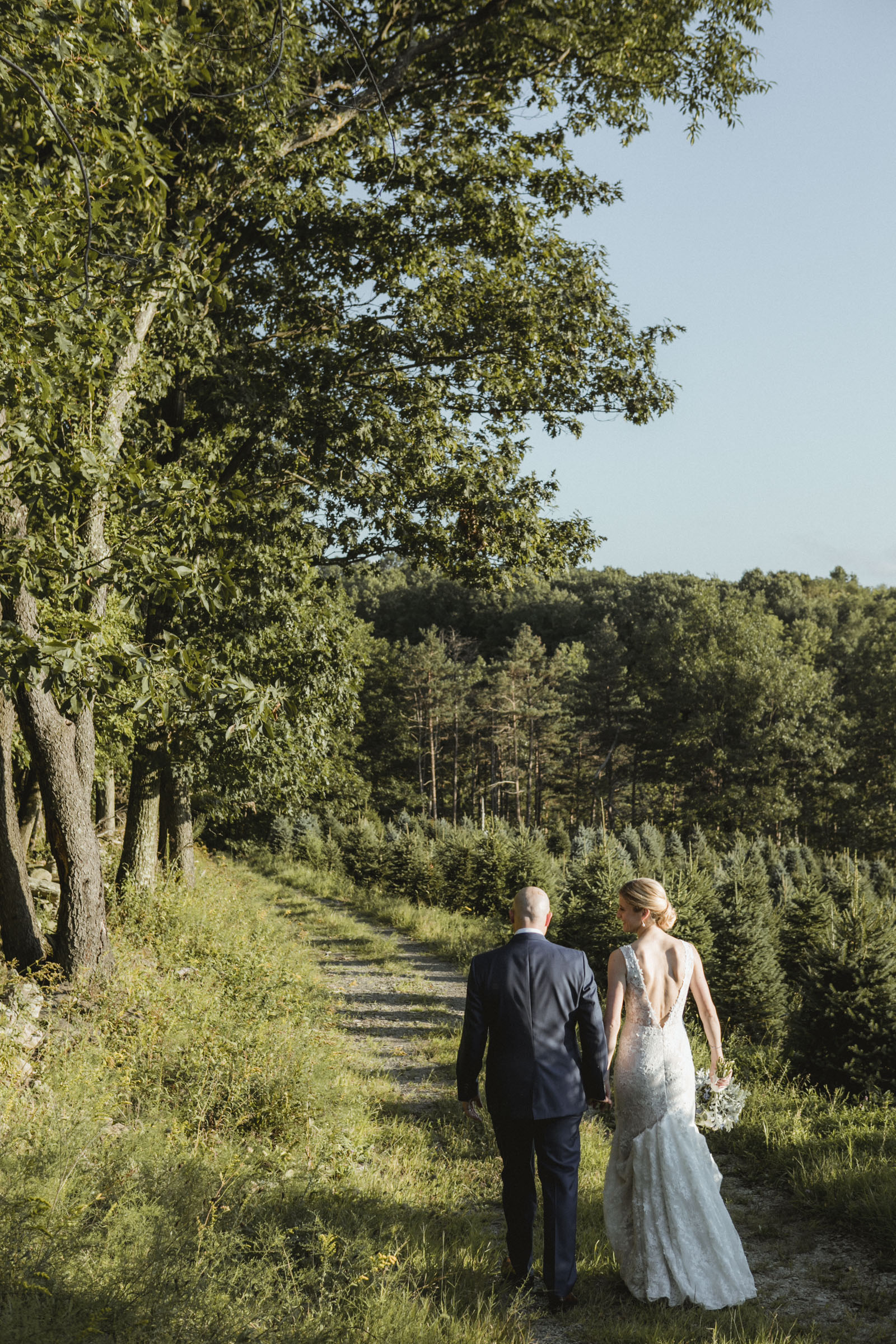 Amy Sims Photography | Bride and Groom walk hand in hand down a grassy path | Emmerich Tree Farm Wedding | Hudson Valley Wedding photographer