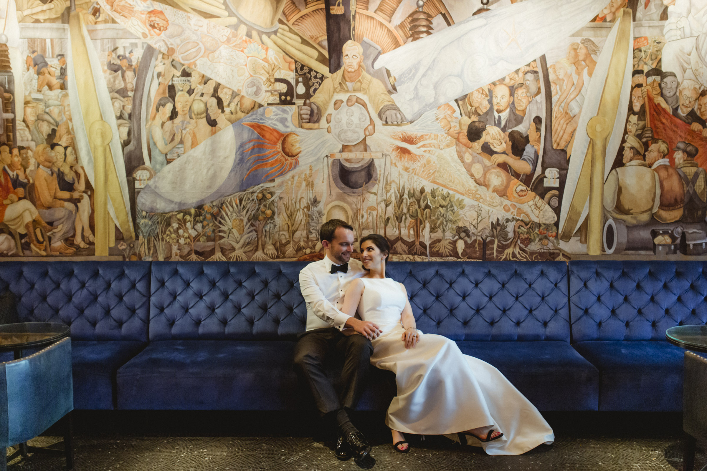 Amy Sims Photography | Bride and groom snuggle on a blue couch under large mural | Public hotel wedding | Manhattan Wedding photographer | New York Wedding photographer