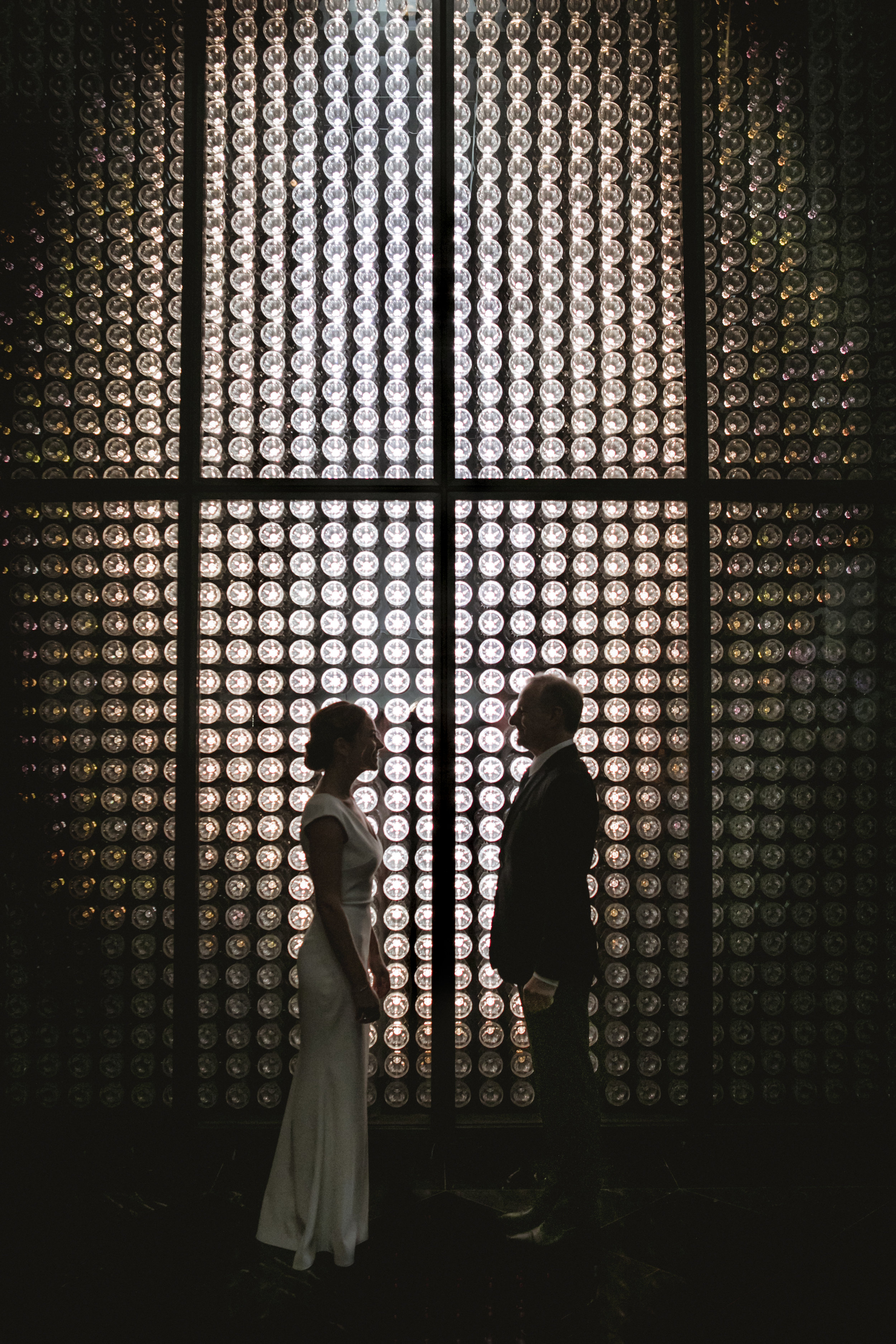 Amy Sims Photography | bride and groom stand facing each other, silhouetted by a wall of lightbulbs | Baccarrat Hotel wedding | Manhattan wedding photographer | intimate wedding photographer | New York wedding photographer