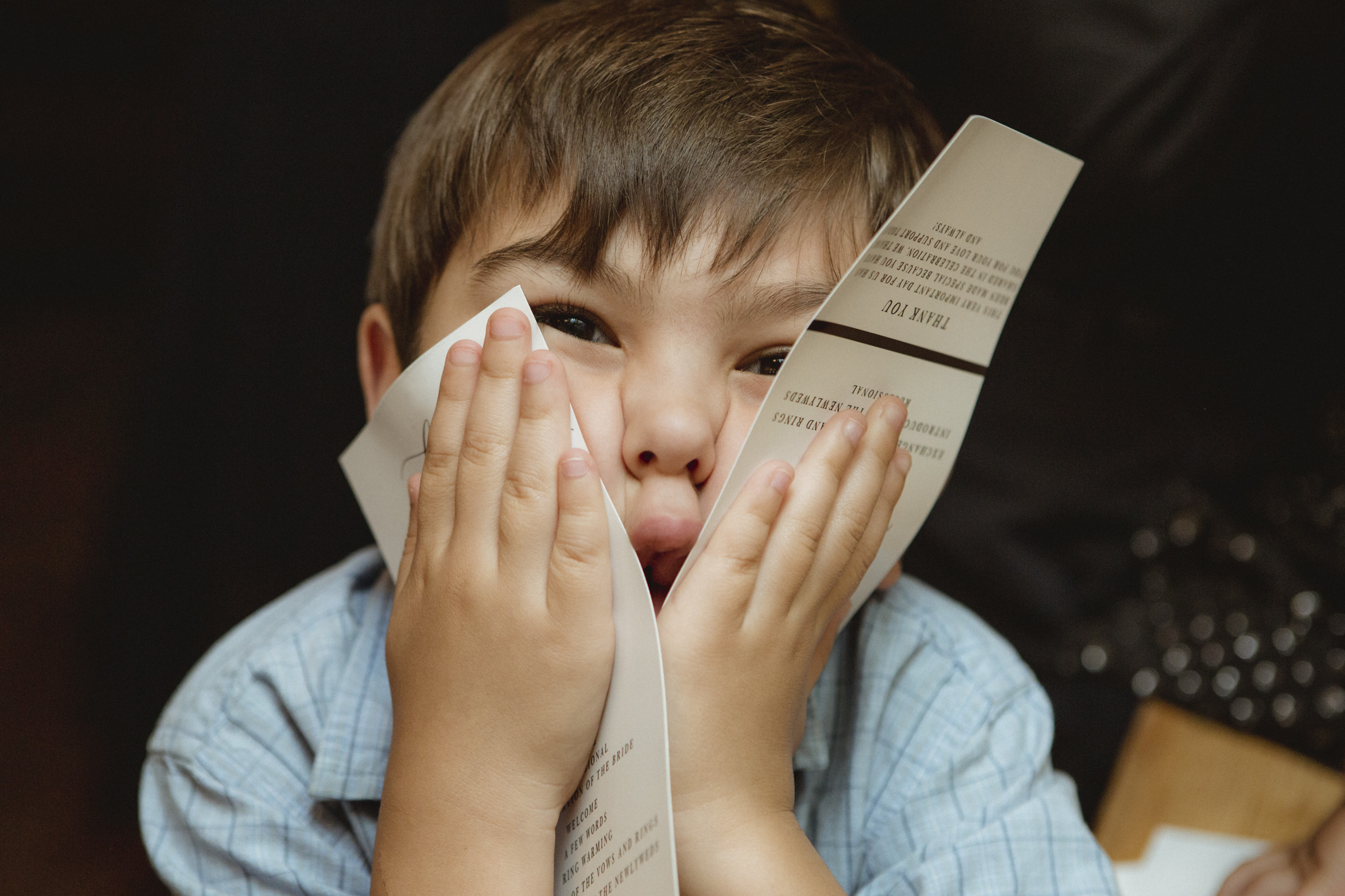 Amy Sims Photography | bored little boy smooshes his face between two paper menus | Brooklyn Winery Wedding | Brooklyn wedding photographer | candid wedding photographer