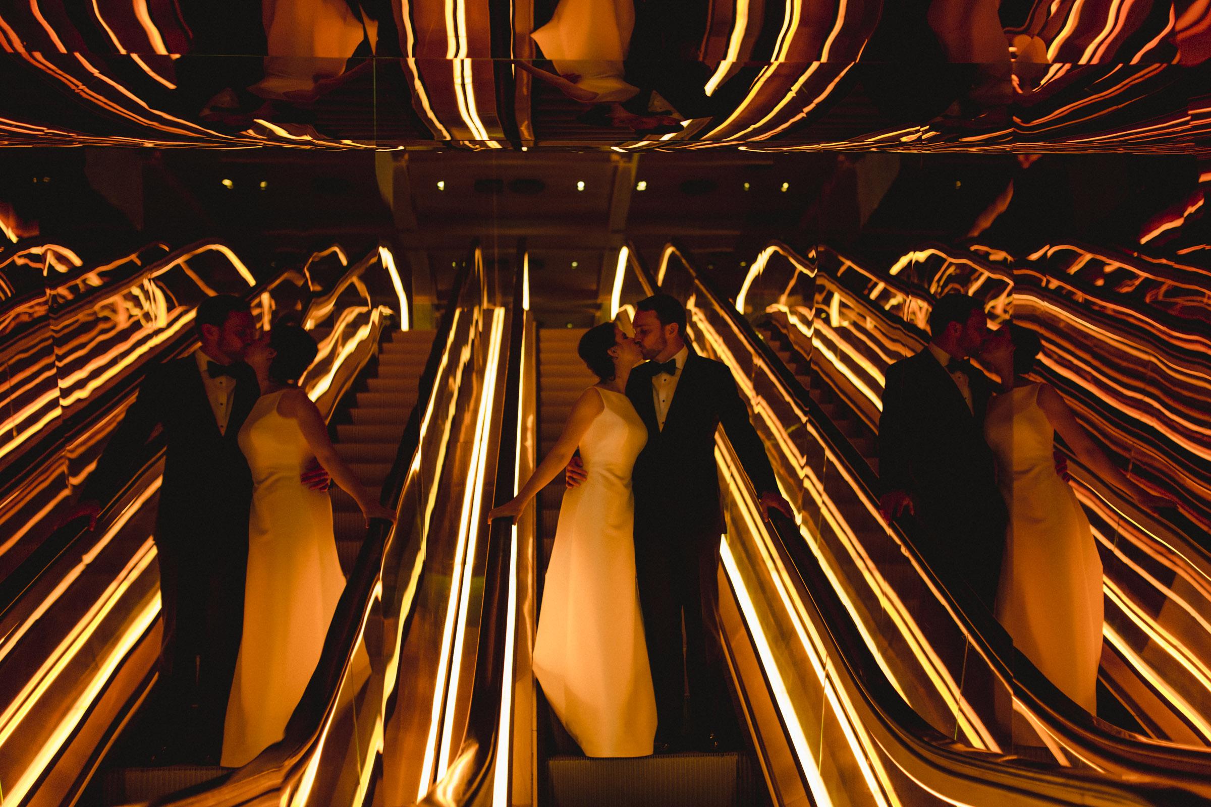 Amy Sims Photography | Bride and groom share a kiss on an escalator bathed in orange light | Public hotel wedding | New York Wedding photographer | Manhattan wedding photography