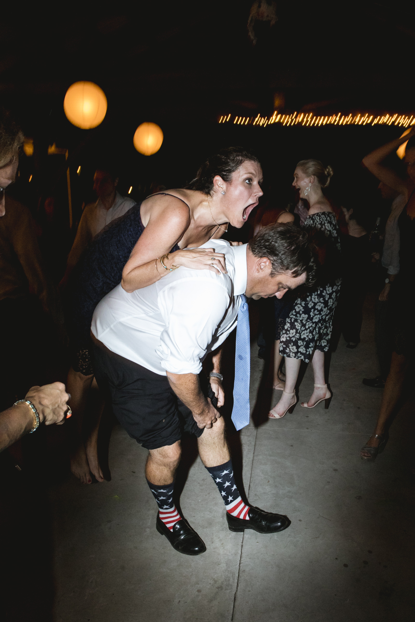 Amy Sims Photography | bridesmaid shouts and she tries to jump over another guests back, as he rolls up his pant legs | Emmerich Tree Farm wedding | Hudson Valley wedding photographer | New York Wedding photographer