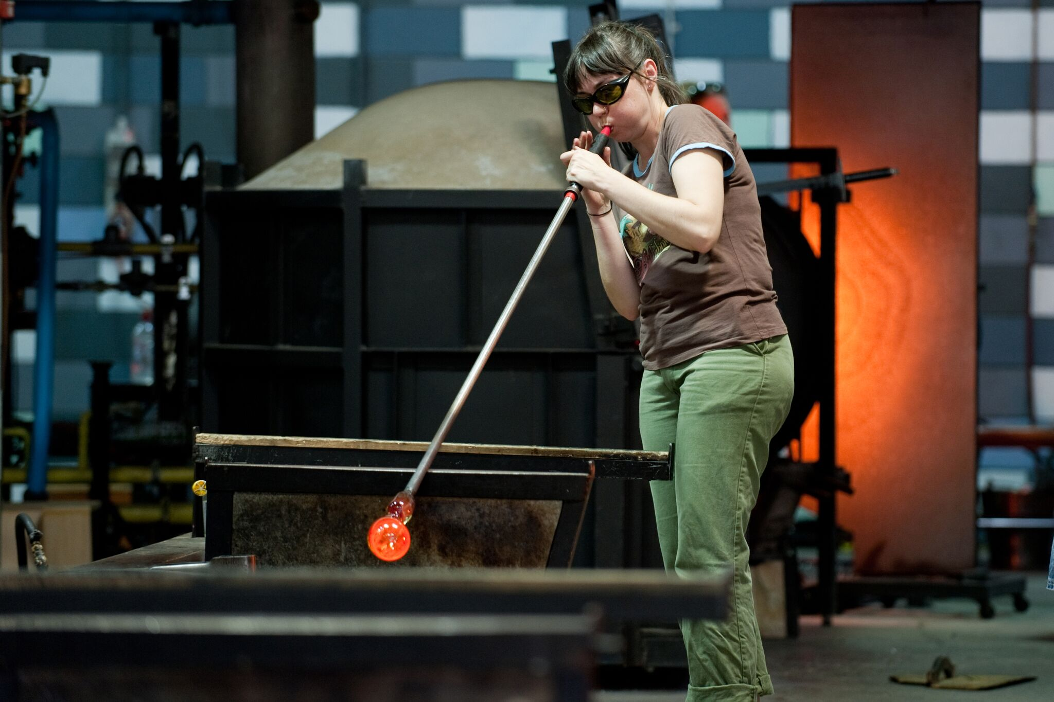 Yhonnie Scarce blowing glass in the hotshop at JamFactory, Adelaide. Photo by Jane Grose. Courtesy the artist.