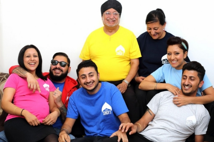 Hi we are the Singh family from East London. In this picture we are most likely attempting to do a fake laugh for the camera and then real laughing at ourselves! From left to right: PINK - Sonia, Neev (in her belly), RED - Rav, BLUE - Butch, YELLOW - Pops, NAVY - Mum, BABY BLUE - Amar and in GREY - Kookie