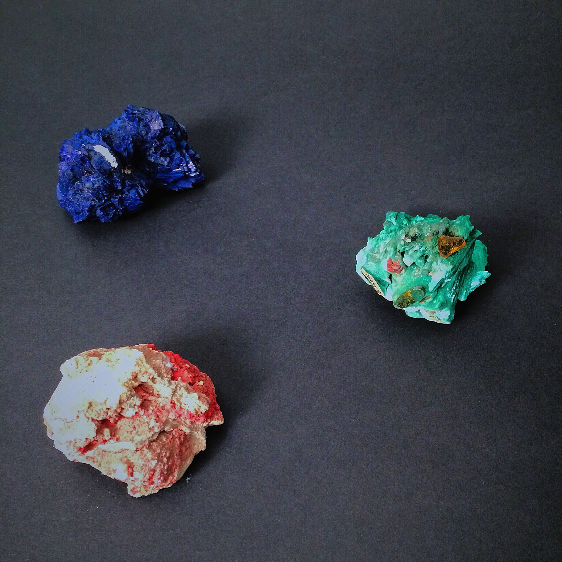 These minerals are idiochromatic. Their color is constant and predictable. Moving clockwise from the top left: azurite, malachite, and cinnabar. Minerals are from the Bruce Museum's collection. Photo by  Haley Royer.