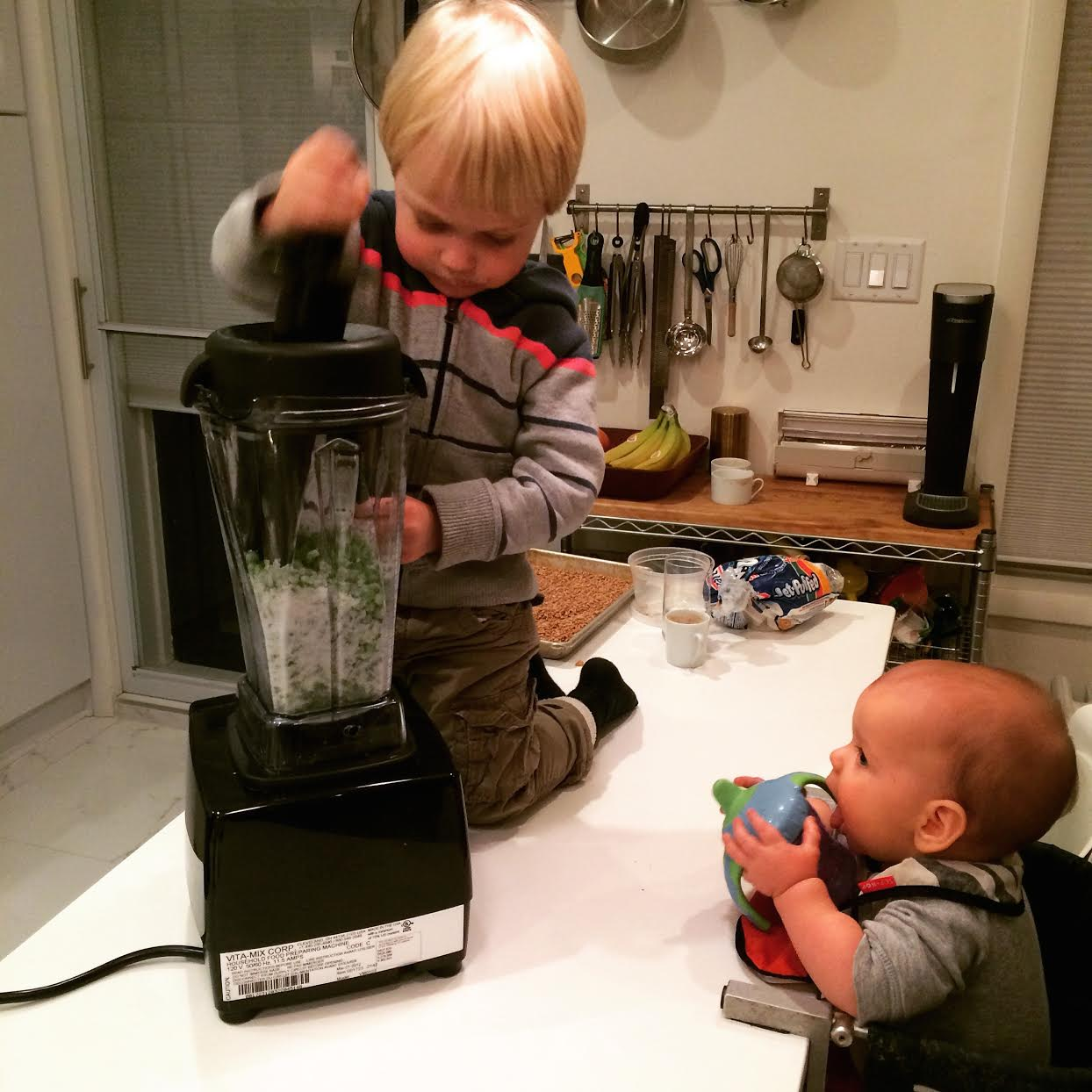 Kid #1 pureeing food for Kid #2. #teachthemyoung.